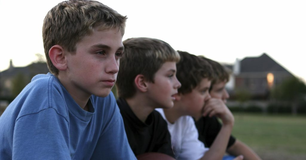 Four boys sitting in a row. Shallow DOF, focus is on first boy.